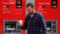 A customer walks past National Australia Bank ATMs. The banks has apologised to customers after a gruelling week of evidence at the royal commission. Photograph: Paul Braven/EPA
